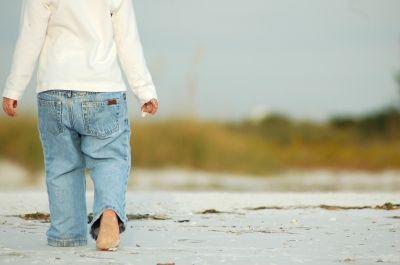 Child walking barefoot on beach